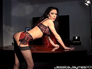 wild brown-haired Jessica Jaymes thumbs her jiggly puss pie in her office